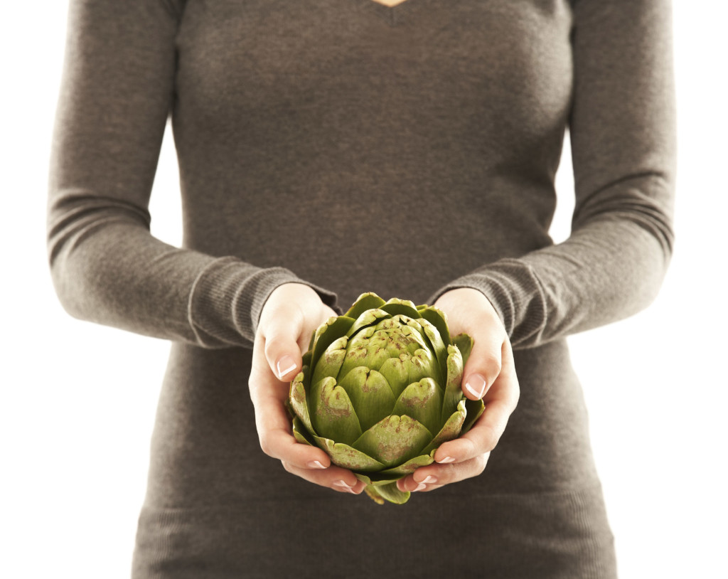 Mid section of a young woman with an artichoke in her hands isolated on white