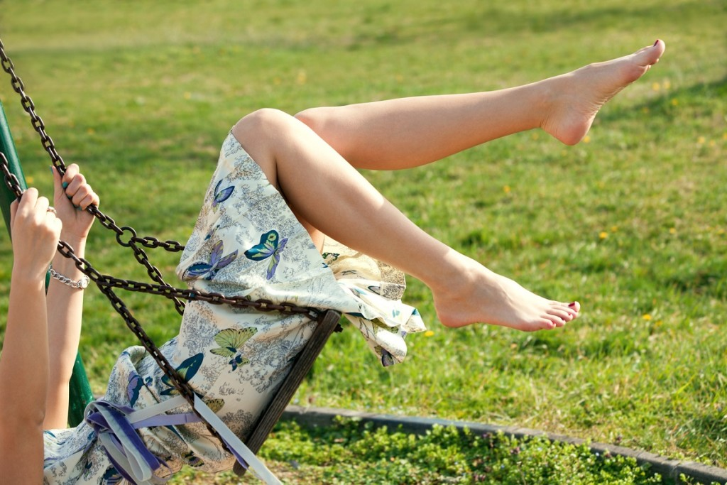 barefoot young woman in dress on swing outdoor in park warm spring day
