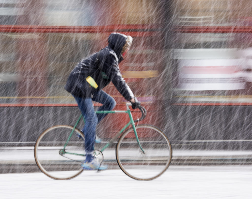 Man on bicycle in the city in snowy winter day. Intentional motion blur