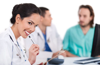Young asian doctor smiling with the pen and looking the camera,